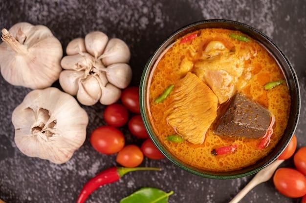 Pollo al curry en una taza negra.