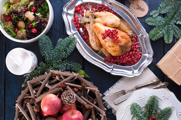 Pollo al horno en una bandeja con frutos rojos. en una mesa de madera azul con un rastrillo