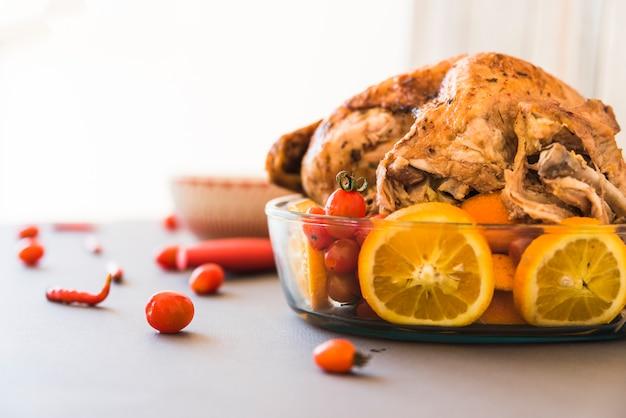 Pollo al horno con naranjas en cristalería