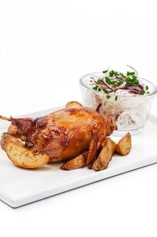 Pollo asado con costra aislado sobre fondo blanco.