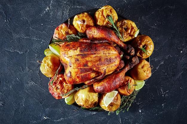 Pollo asado entero servido en un plato negro con manzanas asadas y hierbas aromáticas sobre una mesa de hormigón