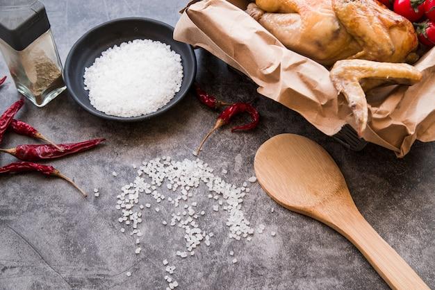 Pollo asado en papel marrón con ingredientes sobre fondo concreto