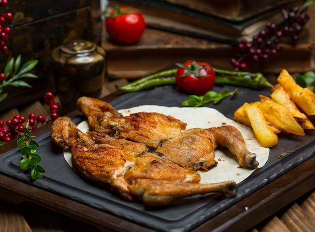 Pollo asado a la parrilla con papas asadas en lavash sobre una tabla de piedra