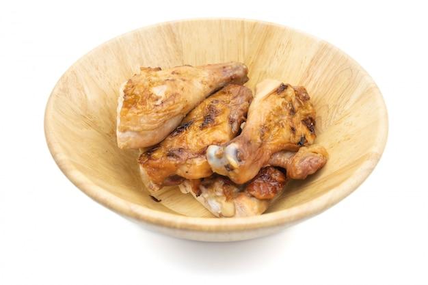 Pollo asado a la parrilla tailandés en el aislante del plato en el fondo blanco, comida tailandesa tradicional