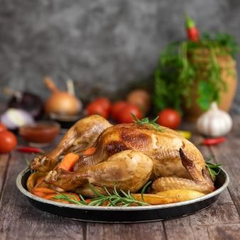 Pollo asado, patatas y verduras en plato sobre madera oscura. vista lateral.