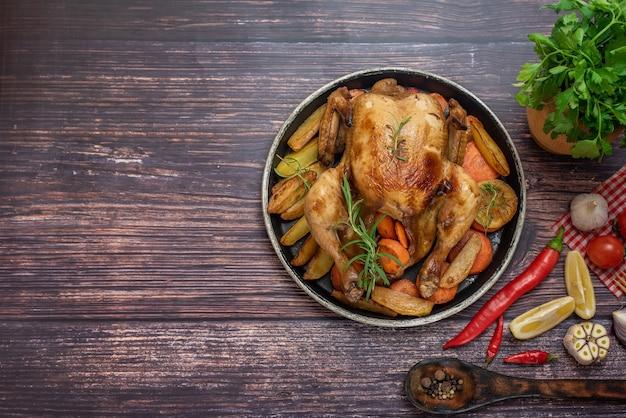 Pollo asado, patatas y verduras en plato sobre madera oscura. vista superior.