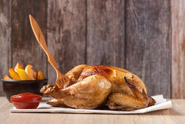 Pollo asado, patatas y verduras en plato sobre madera. vista lateral.