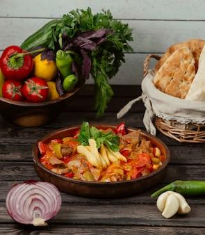 Pollo asado con pimientos, cebolla y tomate en una sartén de cerámica