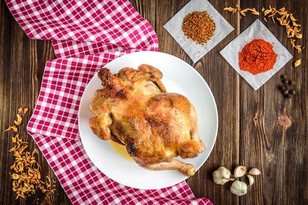 Pollo asado sobre fondo de madera oscura con especias y ajo