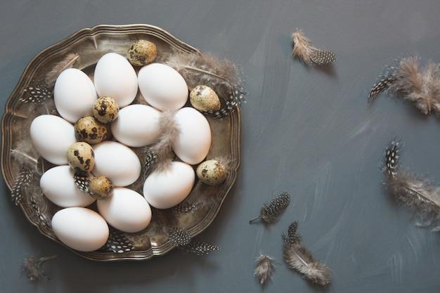 Pollo blanco y huevos de codorniz en placa vintage sobre superficie gris