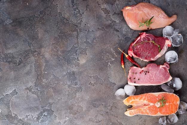 Pollo, carne y pescado crudos con hielo y especias aisladas en piedra. proteínas magras.