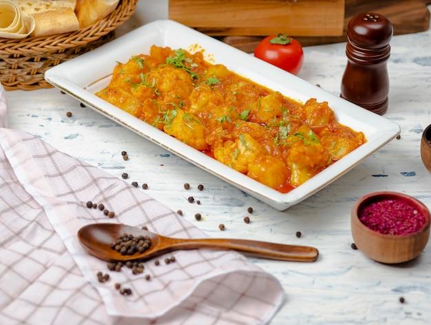 Pollo cocido en salsa de tomate y cebolla.