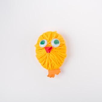 Pollo confeccionado con bola de hilo de lana amarilla.