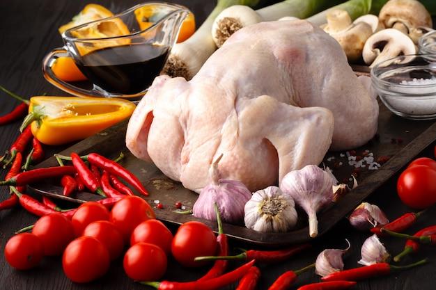 Pollo crudo sin cocinar con ingredientes para cocinar