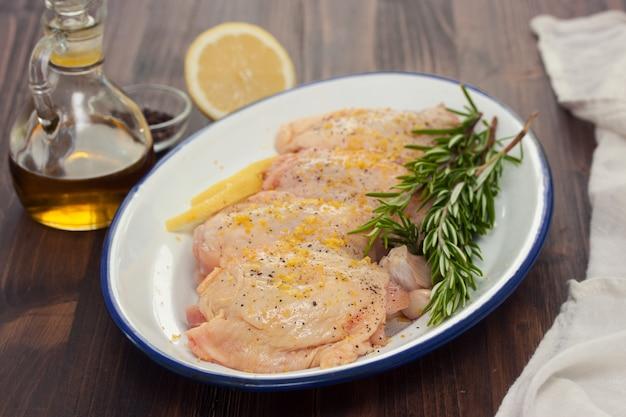 Pollo crudo con limón y romero en plato blanco
