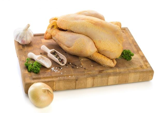 Pollo crudo listo para ser cocinado en tabla de cortar de madera