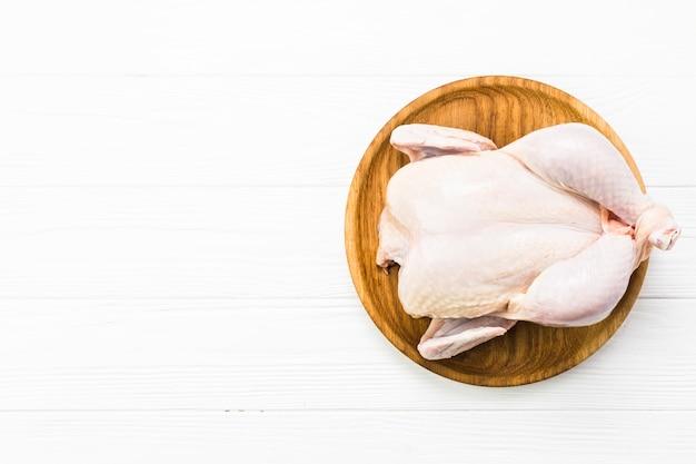 Pollo crudo en plato de madera