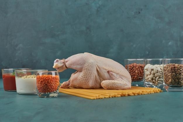 Pollo crudo sobre pasta con frijoles y salsas.
