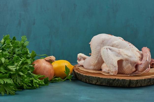Pollo crudo sobre una tabla de madera con hierbas.