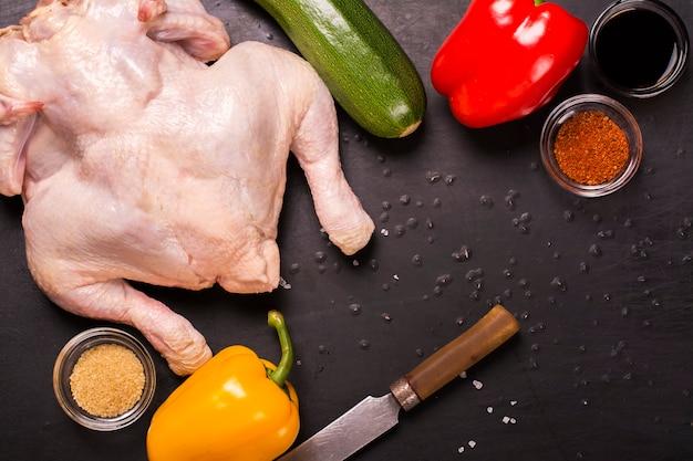 Pollo crudo, verduras y especias.