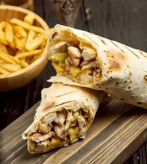 Pollo duro, shaurma con lavas y papas fritas sobre tabla de madera