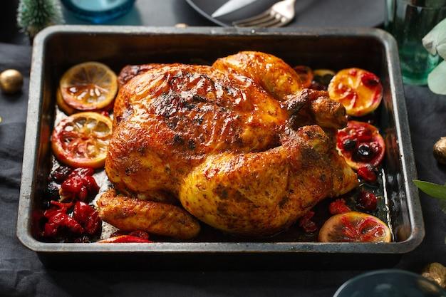 Pollo entero al horno apetitoso con naranjas y arándanos en forma de horno. de cerca