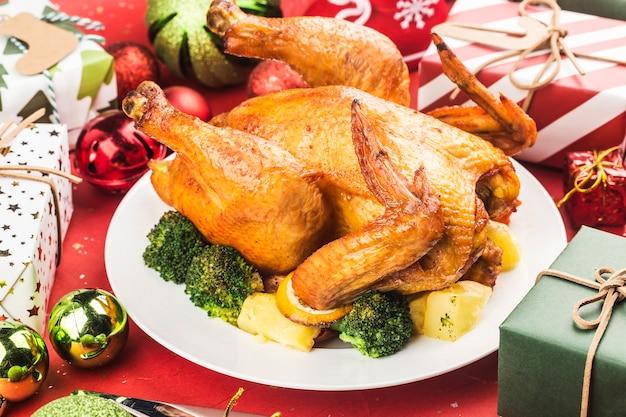 Pollo entero asado con decoración navideña.