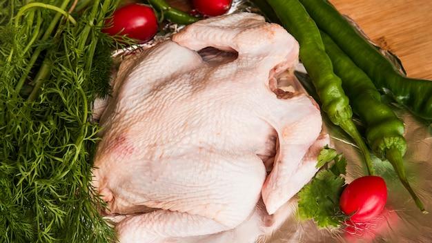 Pollo entero crudo e ingredientes en mesa de madera