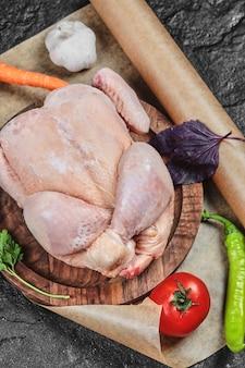 Pollo entero crudo en placa de madera con verduras frescas