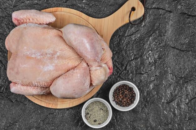 Pollo entero crudo sobre tabla de madera con especias