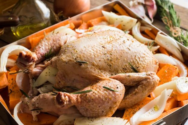 Pollo entero crudo con verduras picadas zanahorias patatas dulces cebollas, sazonadas
