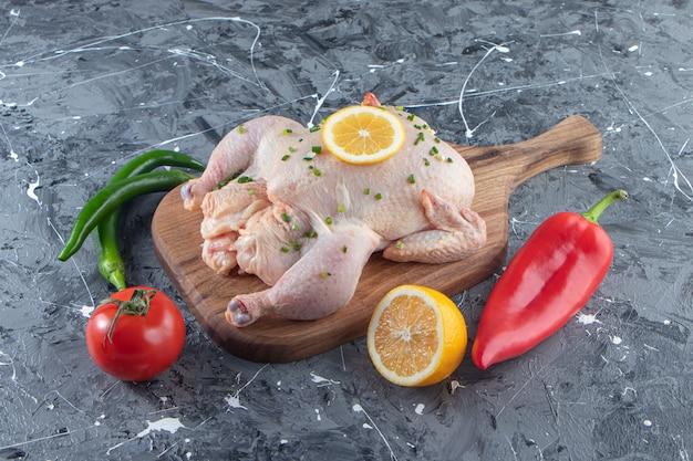 Pollo entero marinado crudo sobre una tabla de cortar junto a verduras, sobre la superficie de mármol.