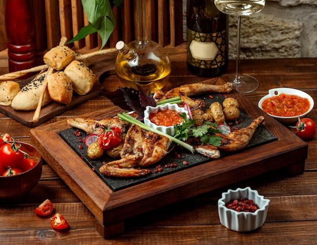 Pollo entero a la parrilla servido con salsa de tomate sobre tabla de piedra
