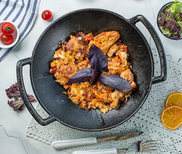 Pollo frito con albahaca en la sartén