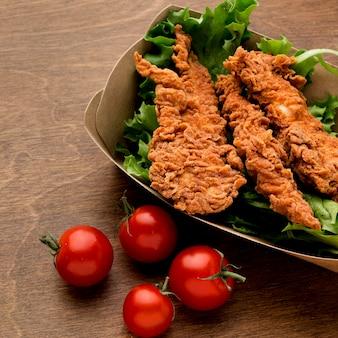Pollo frito de alto ángulo con ensalada y tomates