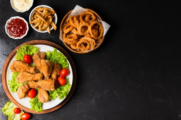 Pollo frito y aros de cebolla con espacio de copia