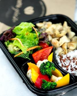 Pollo frito con arroz y verduras.