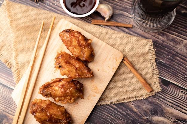 Pollo frito asado coreano caliente y picante en la tabla de cortar de madera