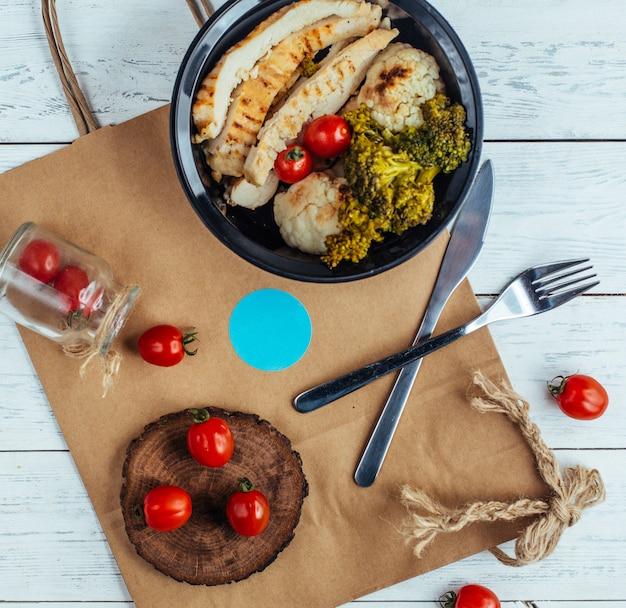 Pollo frito con brócoli y tomates sobre tabla de madera