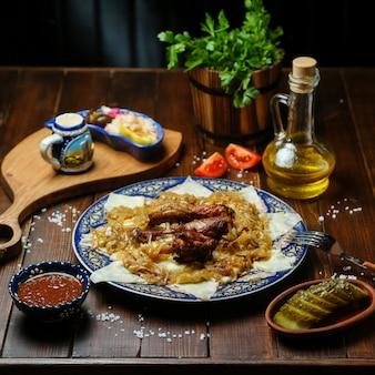 Pollo frito con cebolla en la mesa