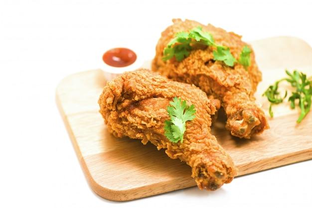 Pollo frito crujiente en placa de madera con salsa de tomate