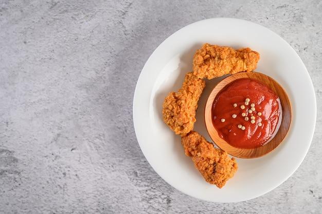 Pollo frito crujiente en un plato blanco con salsa de tomate