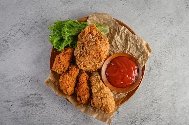 Pollo frito crujiente en un plato de madera con salsa de tomate