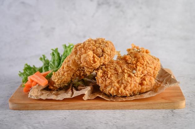 Pollo frito crujiente sobre una tabla para cortar madera