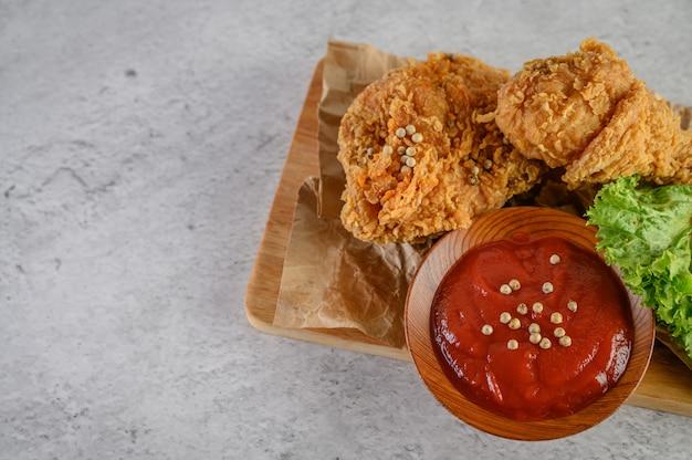 Pollo frito crujiente sobre una tabla de cortar con salsa de tomate