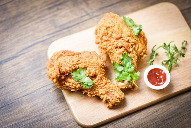 Pollo frito crujiente en el tablero de madera de la placa con la salsa de tomate en la comida de la mesa de comedor