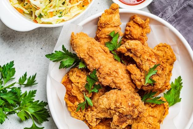Pollo frito crujiente en un tazón blanco con ensalada de ensalada de repollo y salsa.