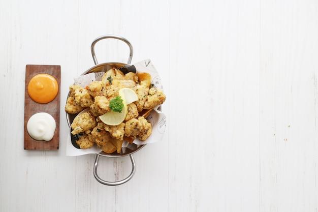 Pollo frito con limón con mayonesa en la sartén sobre la mesa de madera blanca