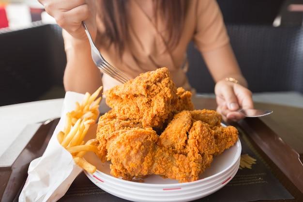 Pollo frito en mano de mujer joven seleccionar el foco