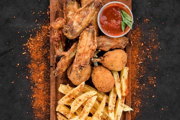 Pollo frito y papas fritas con especias.